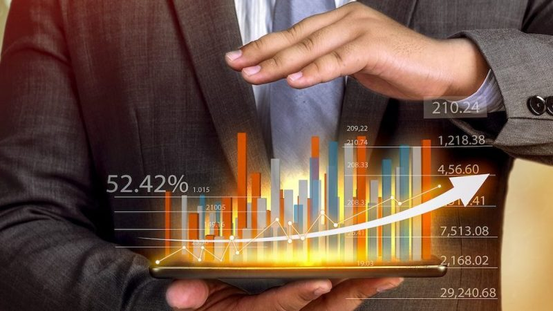 Business people hold a tablet, plan and strategy and display virtual holograms of statistics, financial graphs, securities and charts on a dark background. The concept of business growth